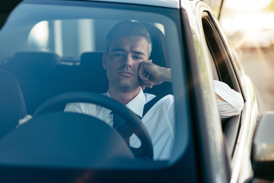Pensive businessman in his car