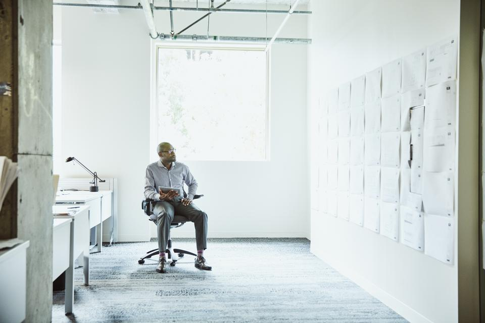 Businessman reviewing project plans on office wall while working on digital tablet