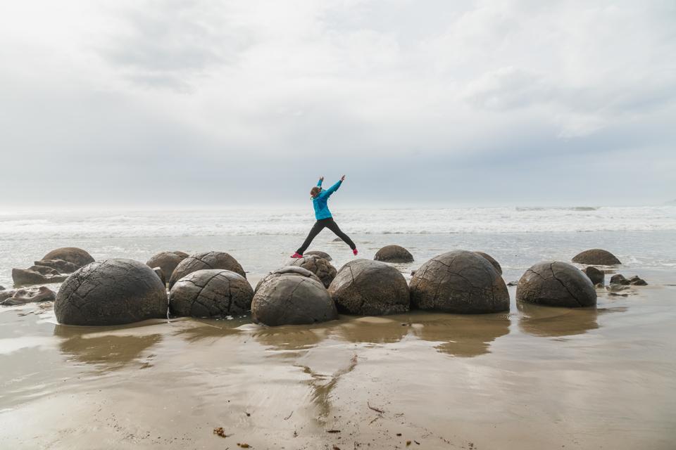 Girl jumping between boulders at Moeraki New Zealand