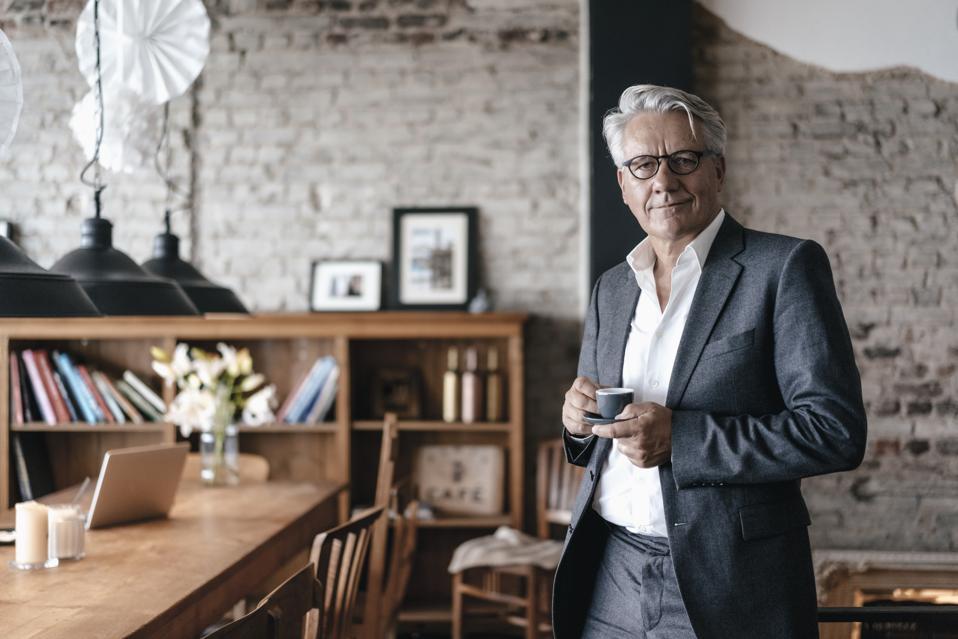Senior businessman drinking coffee, smiling
