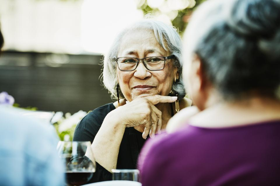 Smiling senior woman in discussion with family during outdoor dinner party