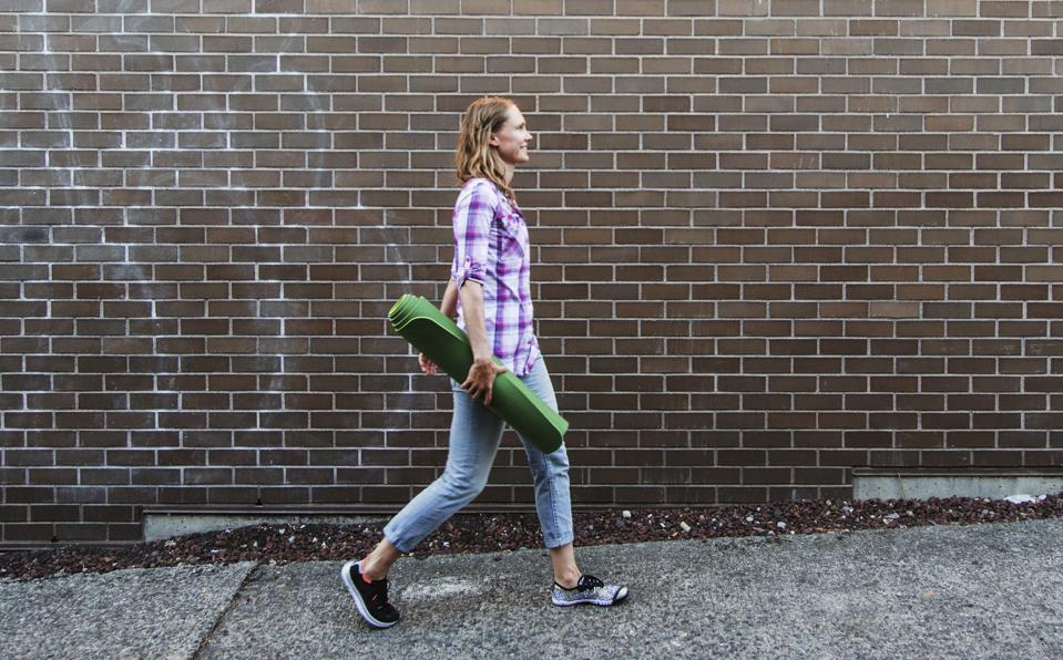 Young woman walking down sidewalk carrying yoga mat, Seattle, Washington State, USA