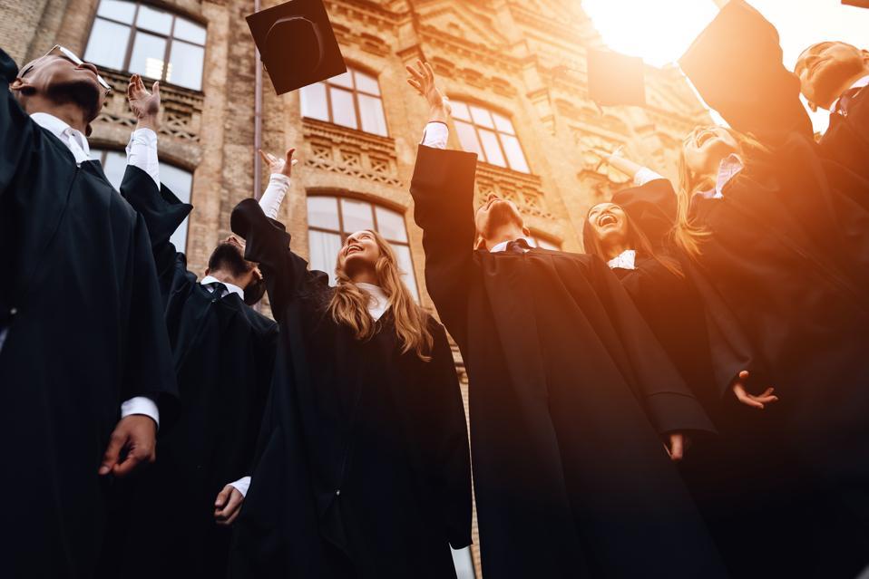 University graduates toss their caps up.