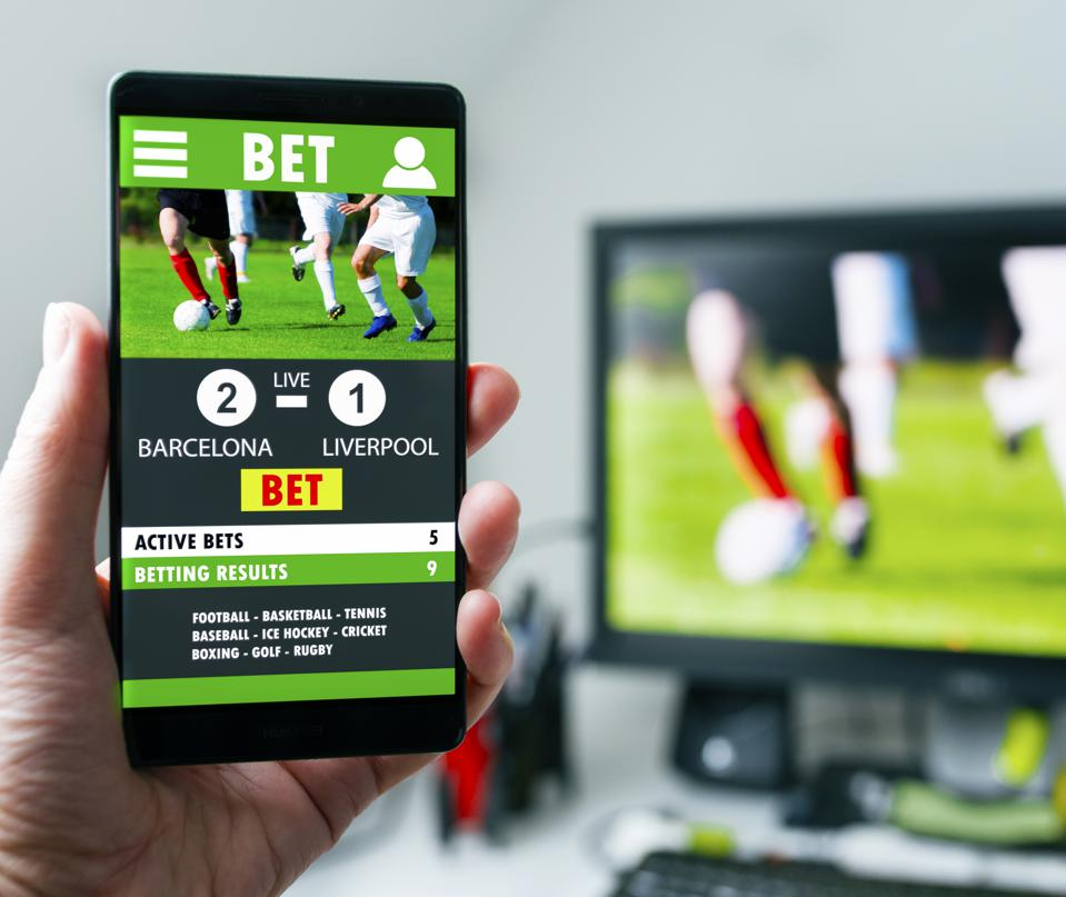 Mobile betting on soccer match on smart phone app in front of a tv screen