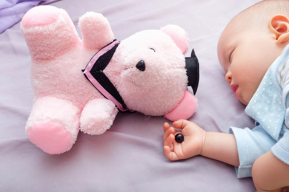 Teddy bear's eye was detached by toddler and in sleeping 10 months old baby hand, beware of choking hazard for children concept