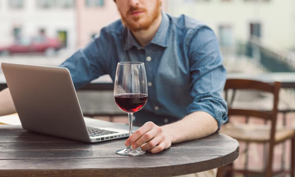Hipster having a glass of wine at the bar