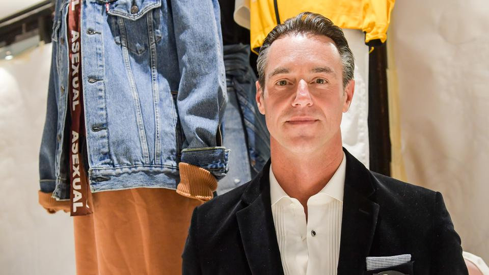 Phluid Project ″A Seat at The Table″. Rob Smith with apparel rails behind him