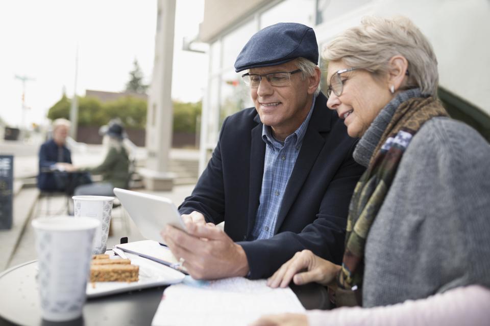 Senior couple using digital tablet at sidewalk cafe