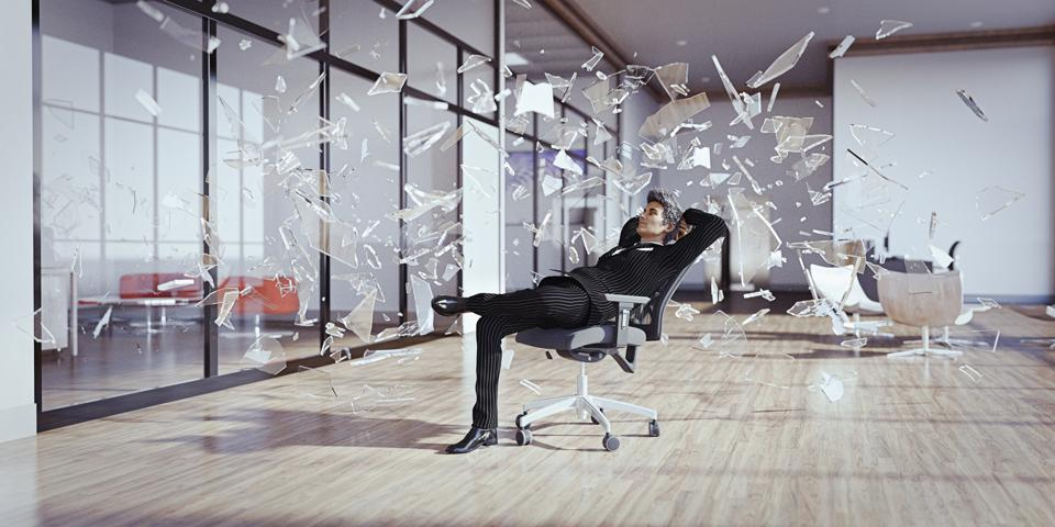 Businessman relaxing chair surrounded by shards of glass