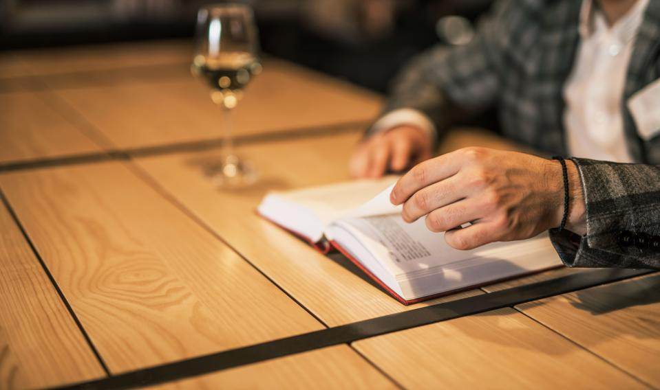 Reading a book with a glass of wine.