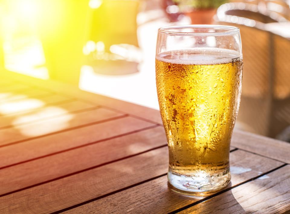 Glass of light beer on the wooden table.