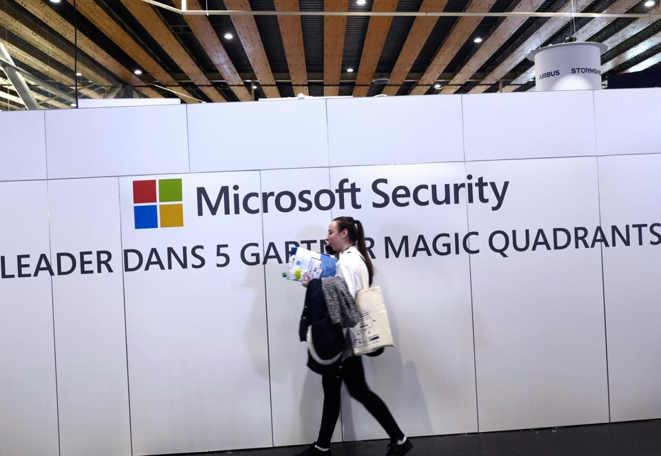A woman walks in front of a Microsoft Security banner