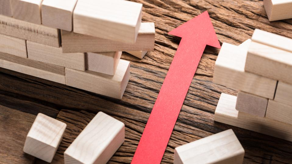 Red Paper Arrow Amidst Blocks On Wooden Table