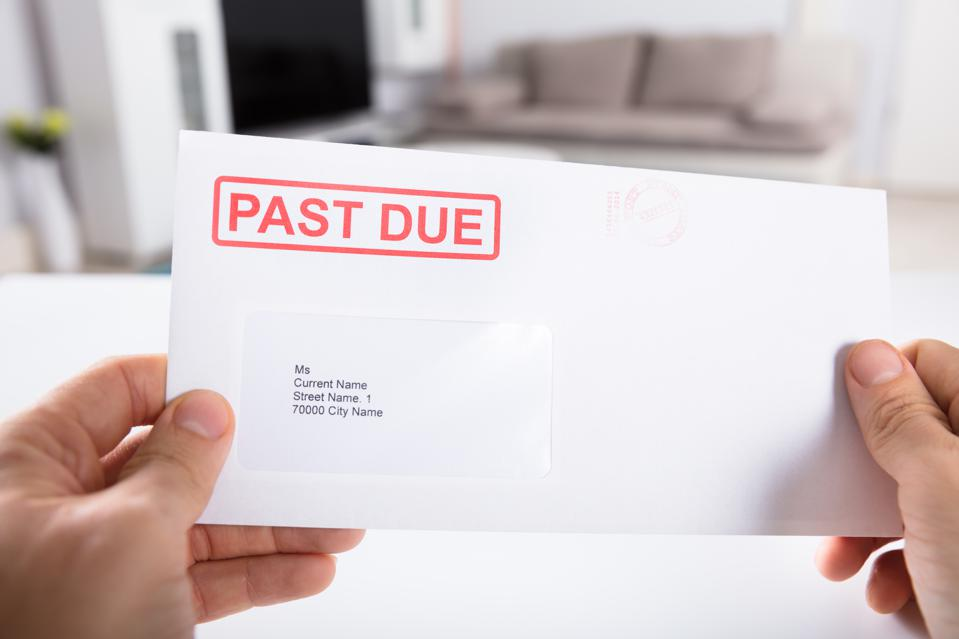 Person Holding Past Due Bill Envelope
