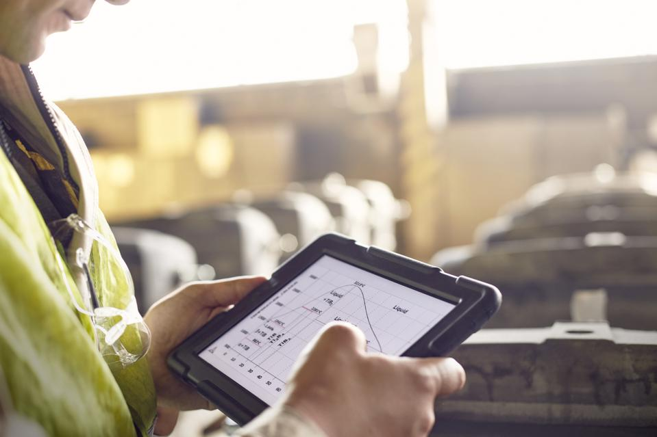 Close up steelworker reviewing digital graph on digital tablet in steel mill
