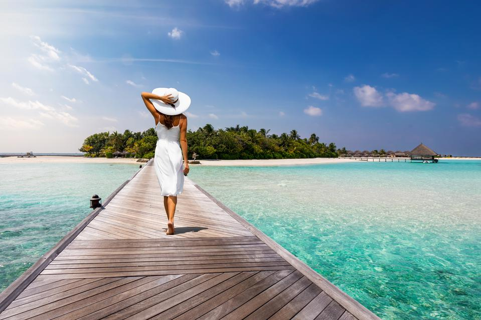 Attractive woman walks over a wooden jetty towards a tropical island