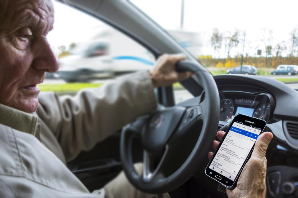 Man at steering wheel checking messages on smart phone while driving.