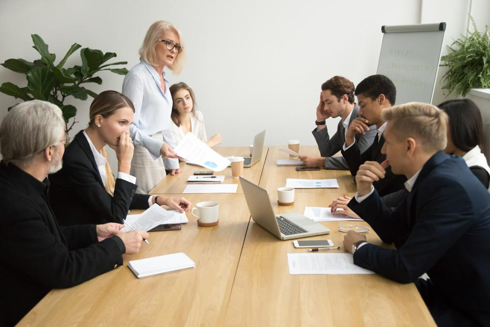 Senior woman boss scolding employees for bad work at meeting