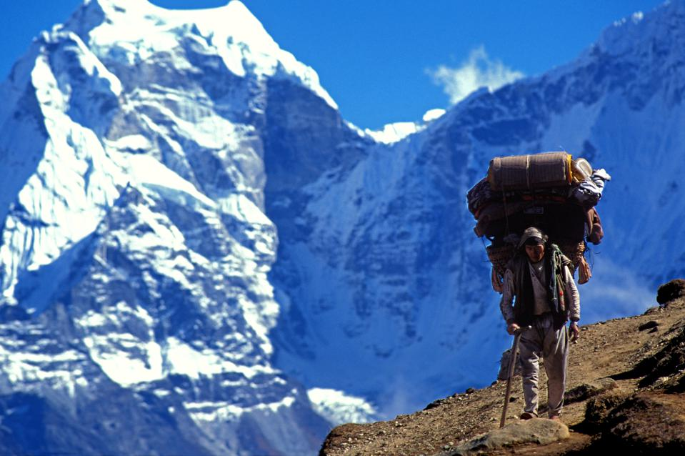 Sherpa carrying bags on an Everest trail. Nepal.
