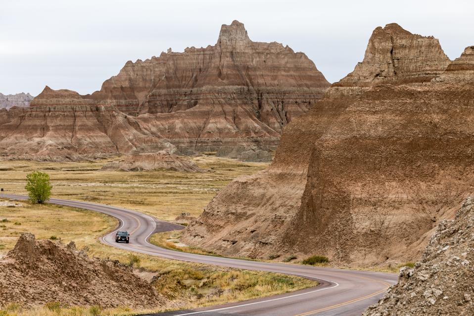 Car Driving along winding road, Badlands National Park, South Dakota, America, USA