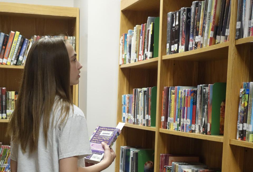 6th Grade Girl Looking at Books in Library