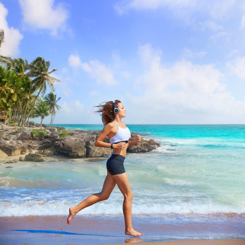 Beautiful brunette girl running in Caribbean beach