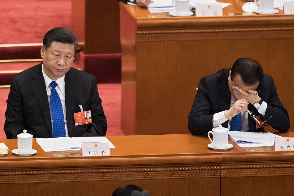 Premier Li Keqiang (R) covers his face in his hand as he and China's President Xi Jinping (L) attend the fourth plenary session of the National People's Congress at the Great Hall of the People in Beijing