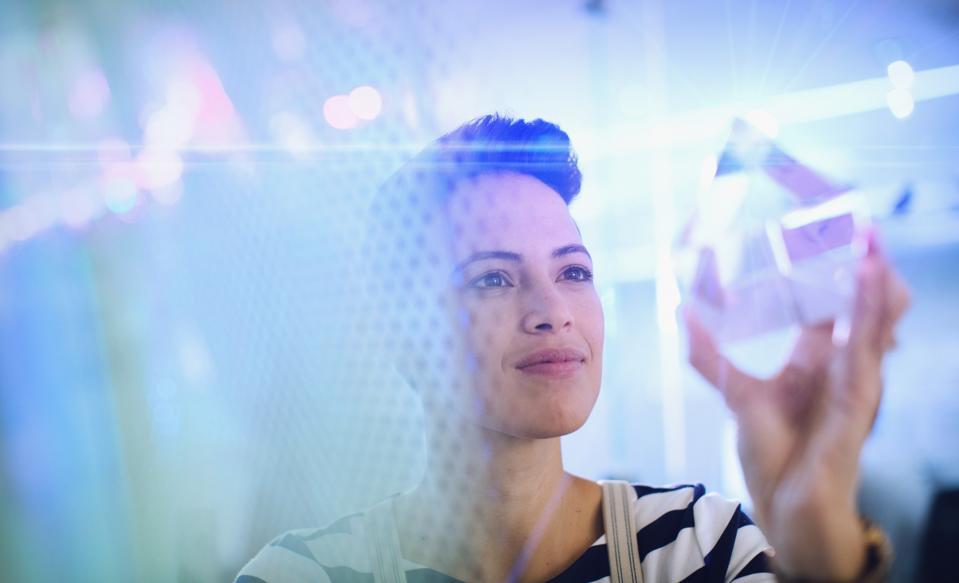 Innovative female entrepreneur examining glass cube prototype