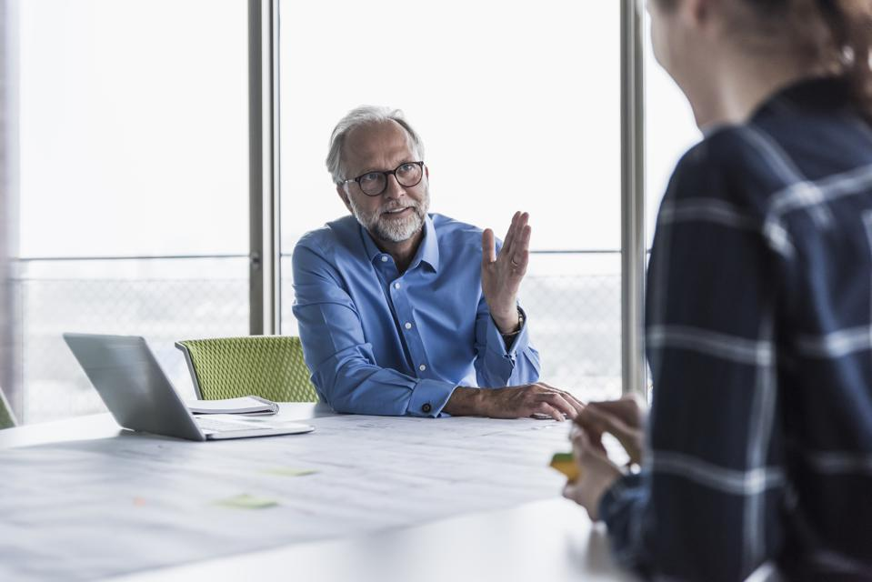Mature businessman and young woman talking in conference room in office