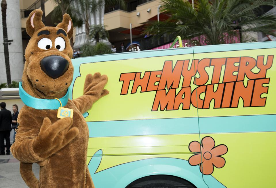 Scooby-Doo standing next to The Mystery Machine van