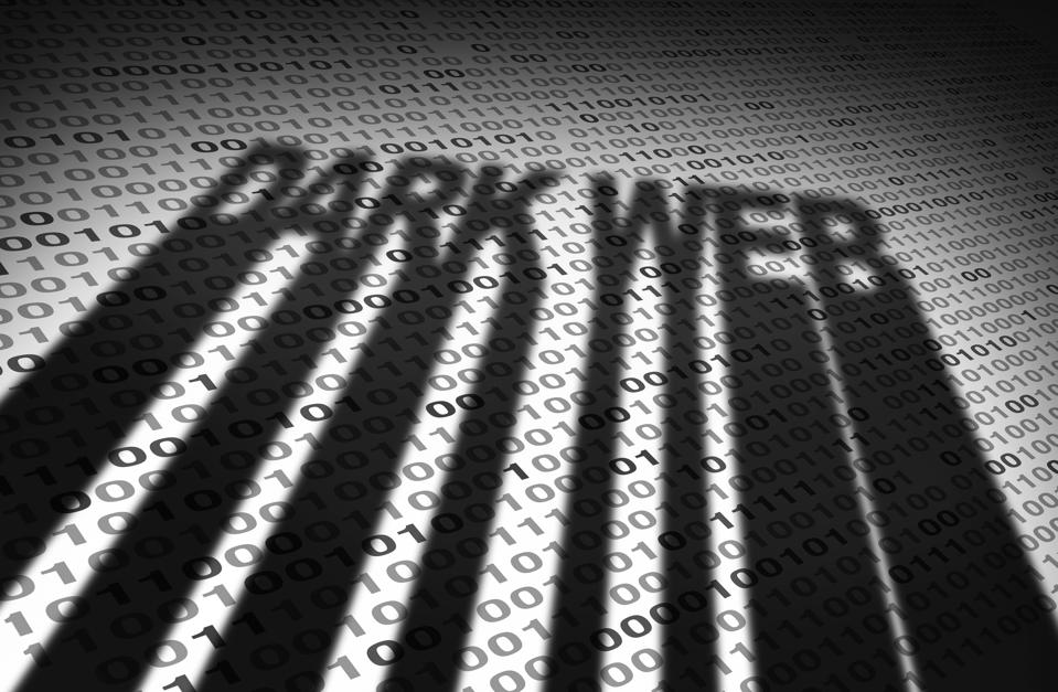 The shadow of the words DARK WEB overlaid on top of a screen of binary code