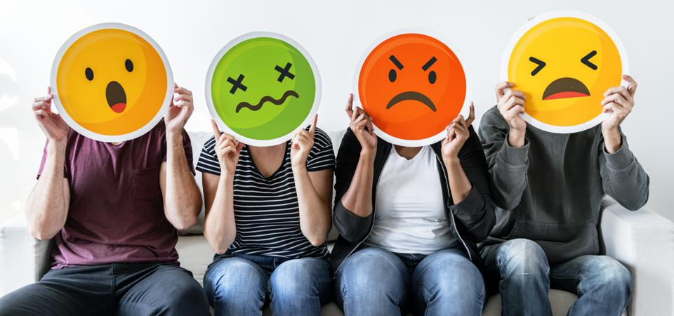 Four seated people in a row, each holding a form of anger emoticon in front of their face.