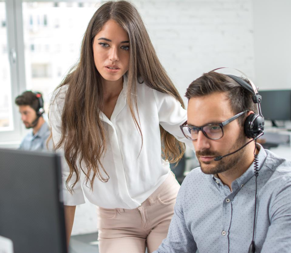 Customer support workers solving problems together on client's online account in call center office.