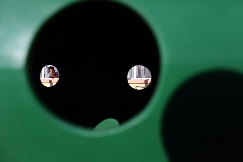 green substance with small holes, with a boy peering through one in the distance
