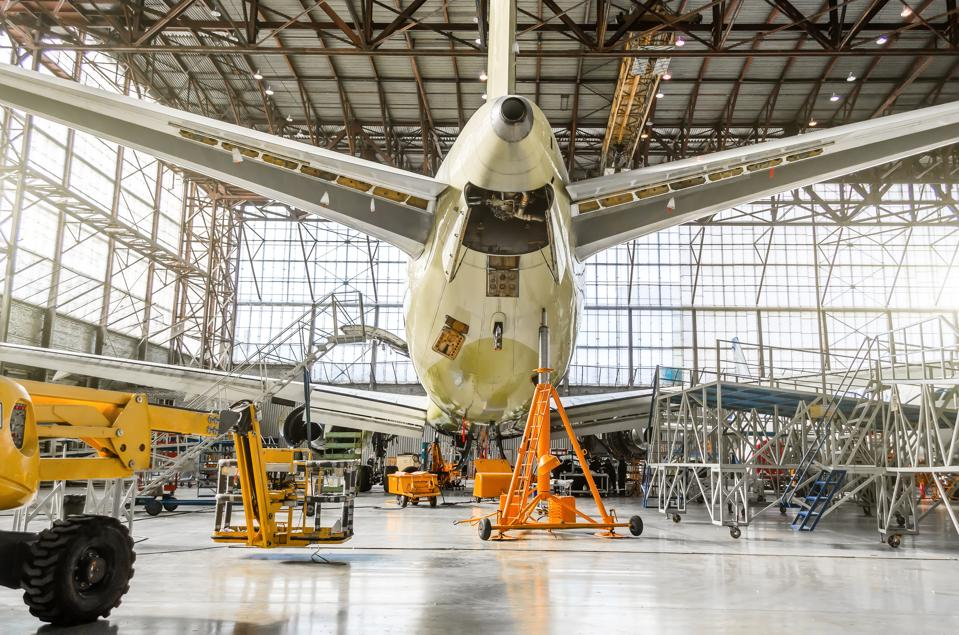 Passenger aircraft on service in an aviation hangar rear view of the tail, on the auxiliary power unit.