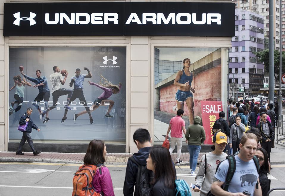Pedestrians walks past American clothing brand Under Armour...