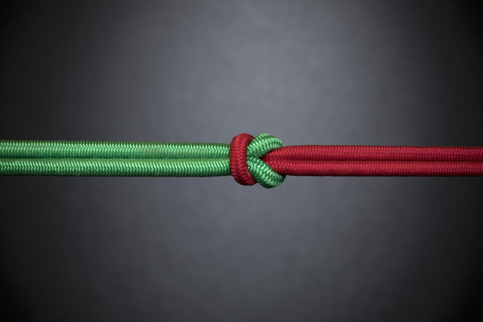 Red and green rope knotted in teamwork, unity