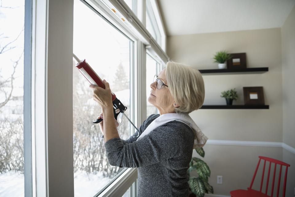 Senior woman weather sealing, caulking windows for winter