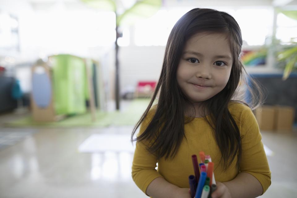 Smiling preschool girl holding markers for preschool.