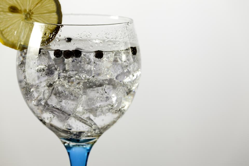 gin tonic on blue glass with lemon and peppercorns detail