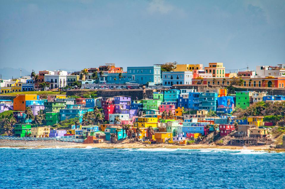 Bright colorful houses line the hills overlooking the beach in San Juan, Puerto Rico