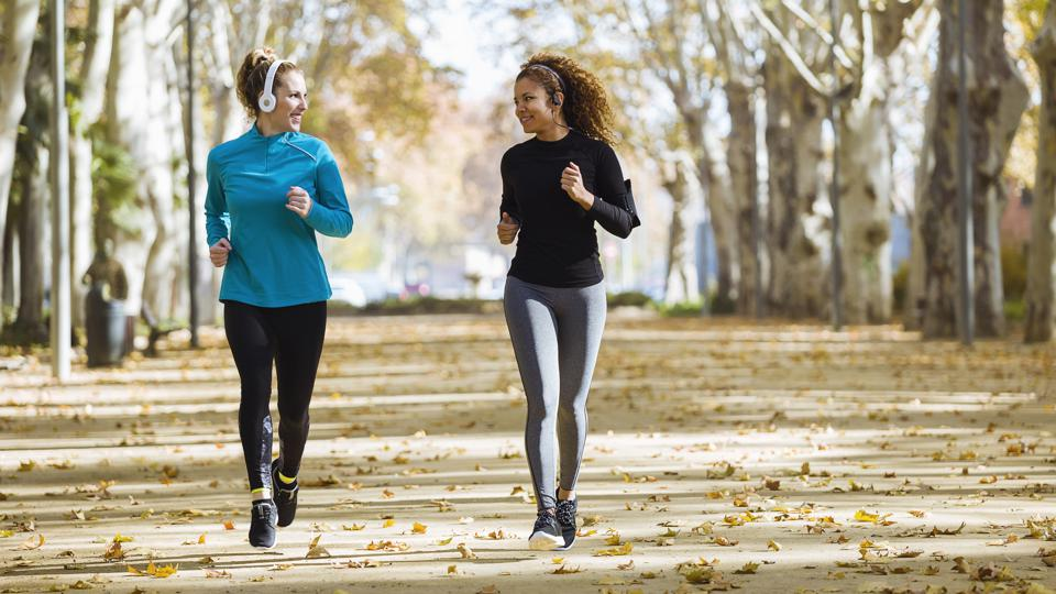 Two smiling young women running in park listening to music