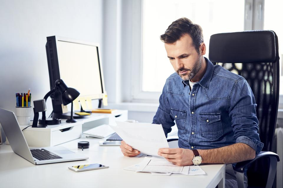 Man reading document at desk in office