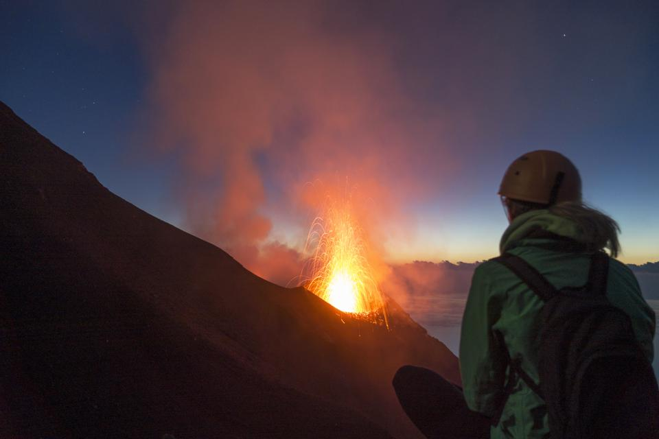Young woman watching volcanos' eruption