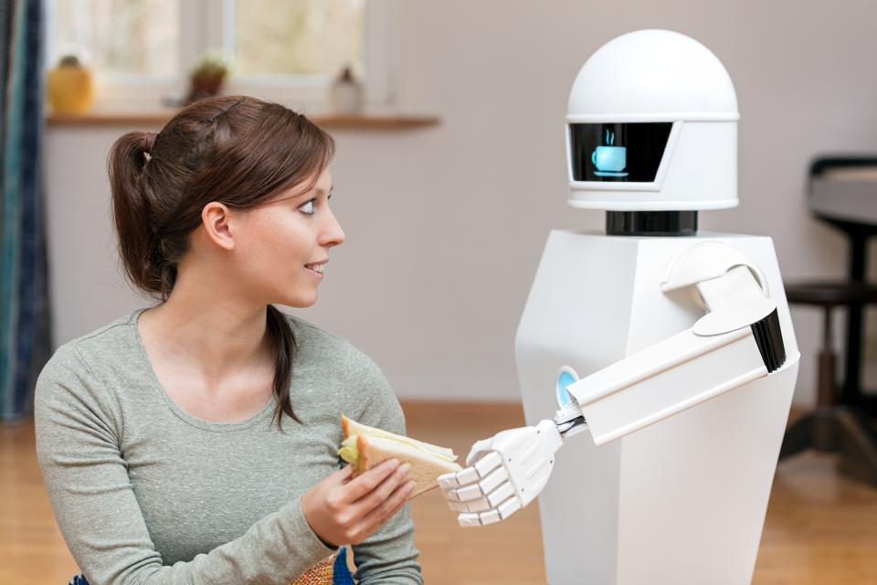 service robot is giving a brunette, pretty woman a sandwich in the living room, display of the household robot is showing a coffee break symbol