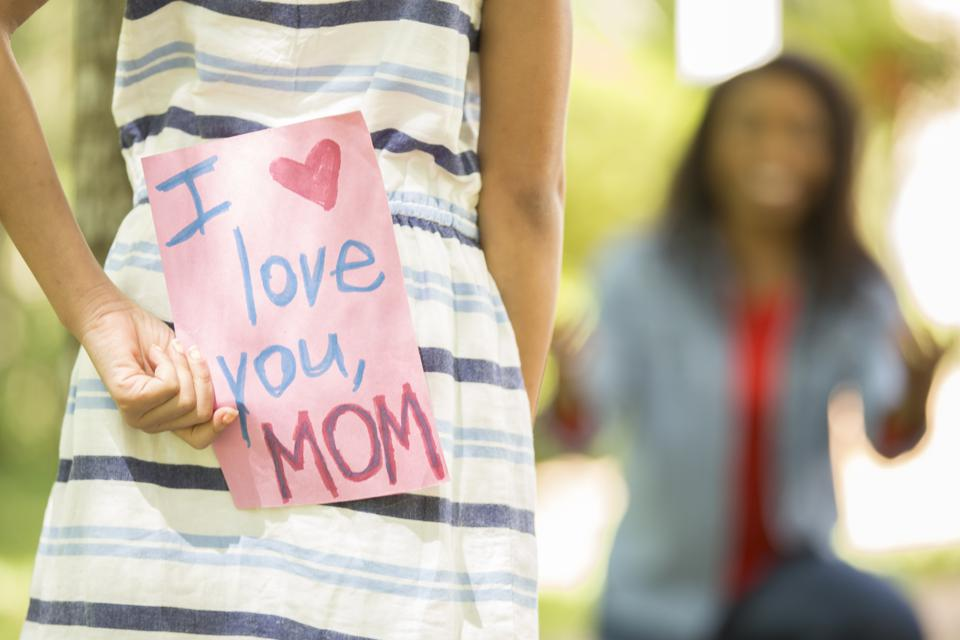 Happy Mother's Day. Girl gives handmade card to mother.