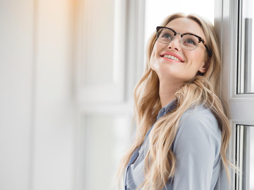 Excited blond businesswoman enjoying peace near window