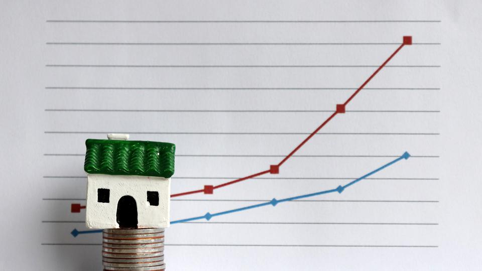 A miniature house on a pile of coins in front of a linear graph. The concept of a relationship between rising house prices and the gap between the rich and poor.