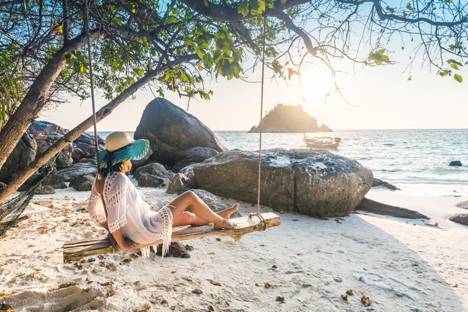 Beautiful woman sitting on swing at the beach, Thailand.