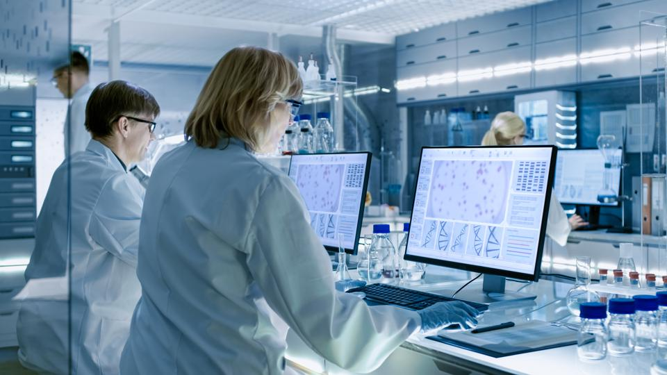 Female and Male Scientists Working on their Computers In Big Modern Laboratory. Various Shelves with Beakers, Chemicals and Different Technical Equipment is Visible.